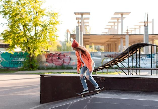 Молодая девушка в полный рост на скейтборде на открытом воздухе
