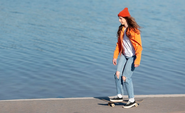 Full shot young girl on skate by the lake