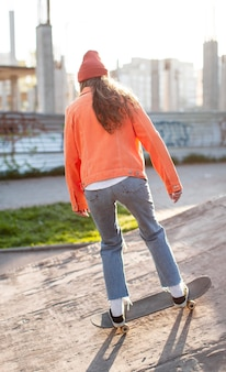 Молодая девушка в полный рост с коньком на улице