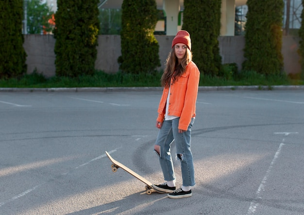 Full shot young girl with skateboard outdoors