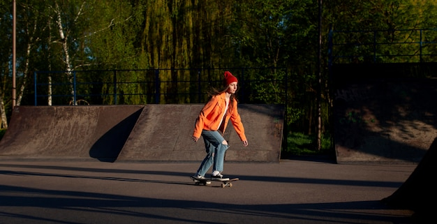 Молодая девушка в полный рост со скейтбордом на улице