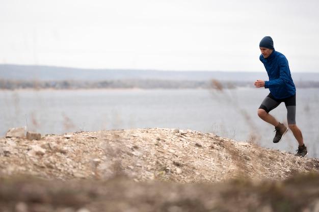 トレイルで走っているフルショットの若い男