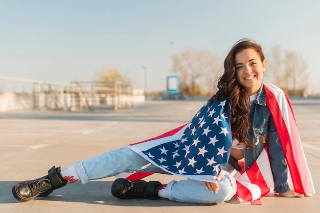 Полная съемка молодая женщина, носить большой флаг сша