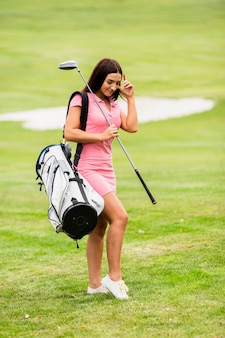 Full shot young woman with golf clubs