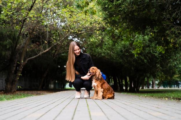 Полный выстрел молодая женщина со своей собакой