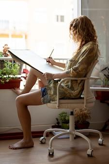 Full shut woman on chair drawing