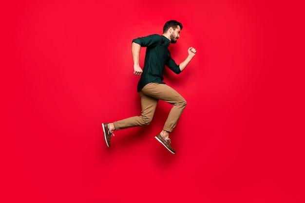 자신감있는 남자 점프 실행의 전체 크기는 모든 봄철 할인을 입고 갈색 바지 바지를 빨리 구입하고 싶습니다.