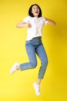 Полноразмерная счастливая молодая азиатская женщина прыгает от радости, показывает в знак одобрения большие пальцы и позирует на желтом фоне в джинсах и повседневной белой футболке