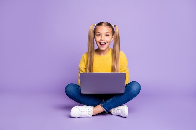 Full size photo of amazed child sit folded crossed legs work computer get social media notification scream wow omg wear yellow pullover sneakers isolated over purple color wall