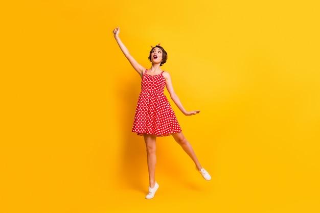 Полноразмерная фотография удивленная милая милая красивая девушка подержать руку попытаться поймать зонтик ветреная погода концепция крик носить красный горошек винтажный стиль наряд обувь изолирована яркая цветная стена