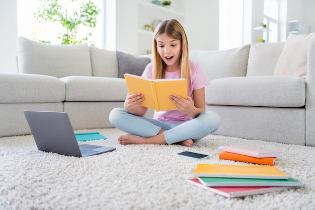Full size photo of astonished pupil sit floor legs crossed folded barefoot carpet read interesting encyclopedia impressed study remote in house indoors