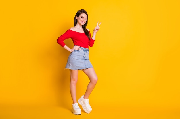Full size photo of attractive pretty girl enjoy weekend holiday make v-sign wear denim red tank top gumshoes isolated over bright shine color background