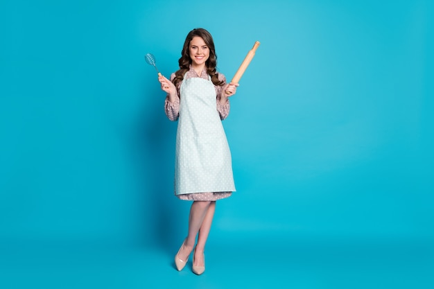 Full size photo of beautiful attractive lady hold hands kitchen utensils mixer rolling pin cooking family cake pie wear apron dotted dress stilettos isolated blue color background