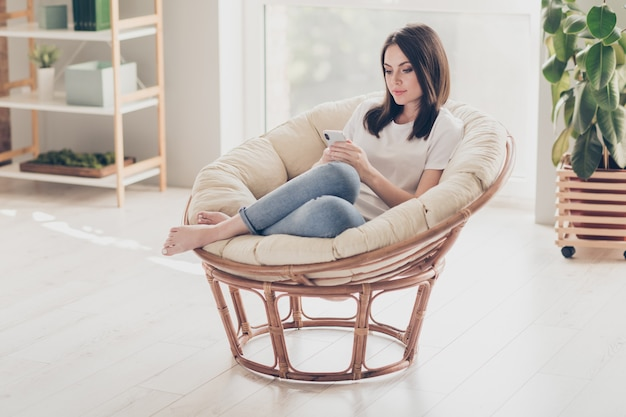 Full size photo of charming girl sit wicker chair chatting with friends on smartphone in house indoors