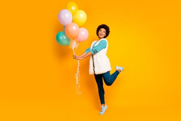 전체 크기 사진 쾌활한 아프리카 미국 소녀 즐길 생일 발렌타인 데이 파티 개최 공기 baloons 착용 흰색 청록색 풀오버 세련된 유행 파란색 바지 바지 절연 광택 컬러 벽