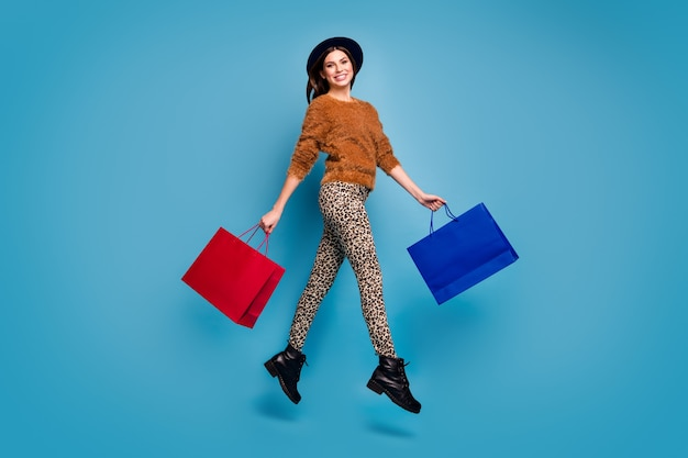 Full size photo of cheerful girl jump walk hold off-sales bargain bags enjoy autumn spring trip wear brown casual sweater pants retro vintage headwear boots isolated blue color wall