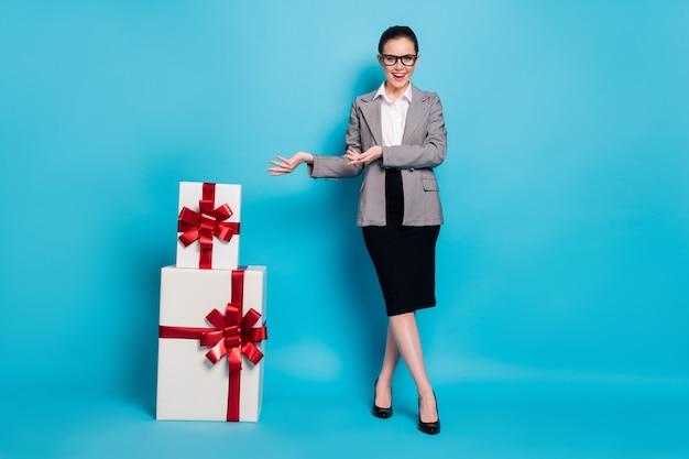 Полноразмерное фото старшая девушка готовит стопку стопки подарочной коробки держать руку носить юбку пиджак пиджак изолированный синий цвет фона