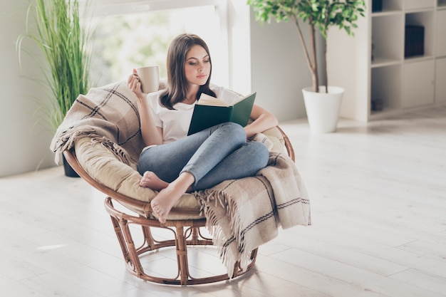 Full size photo of concentrated girl read book sitting on wicker chair with coffee cup wear white t-shirt in house indoors
