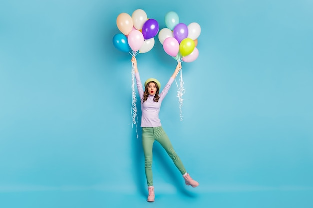 Full size photo of crazy pretty lady hold many air balloons arms raising up wind blowing wear purple jumper beret cap green trousers boots isolated blue color wall