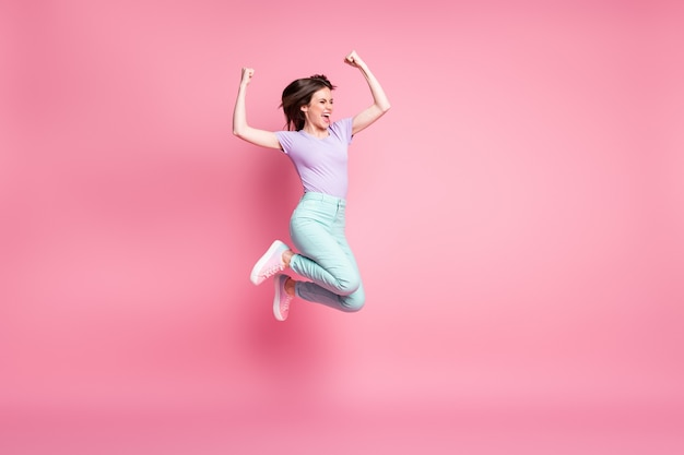 Full size photo of delighted crazy girl jump enjoy lottery win raise fists scream wear turquoise violet trousers sneakers isolated over pastel color background