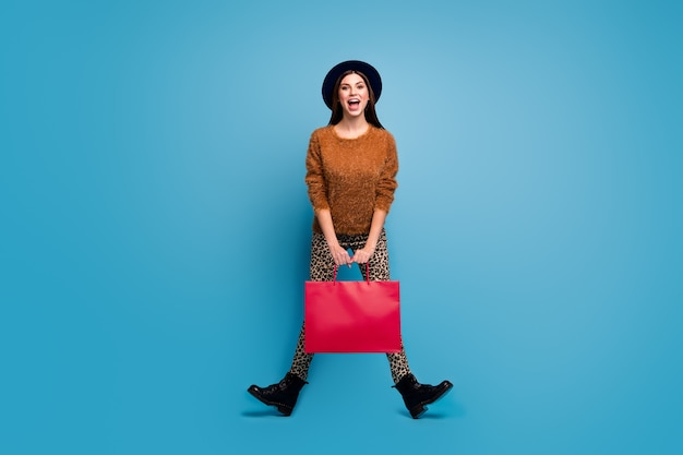 Full size photo of funky crazy girl enjoy fall spring holiday walk shopping hold bags scream wear brown sweater retro vintage style pants boots hat isolated over blue color wall