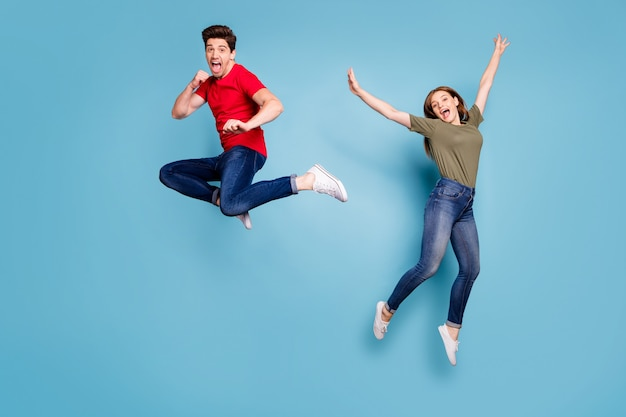 Full size photo of funky crazy two people spouses students man fight kick hands fists woman jump fool raise arms wear green red t-shirt denim jeans sneakers isolated blue color background