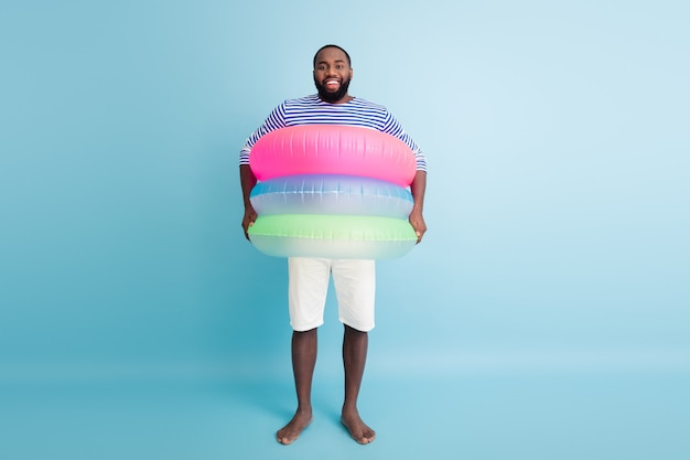 Full size photo of funky funny barefoot afro american guy enjoy  weekend have colorful ring float lifesaver buoy ready swim in ocean wear white shorts frock isolated blue color wall
