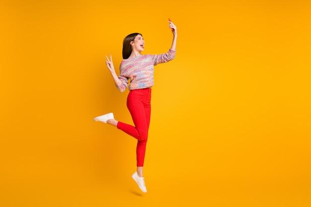 Полноразмерное фото смешная девушка расслабиться осенние каникулы взять селфи смартфон сделать v-знаки видеозвонок блоггеры влиятельные лица носить красные брюки брюки обувь изолированы яркий блеск желтый цвет