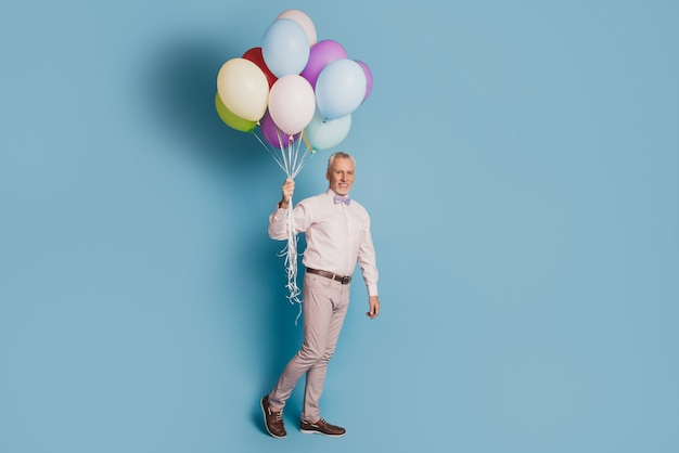 Full size photo gentleman hold many baloons festive wear good look outfit footwear isolated blue color background
