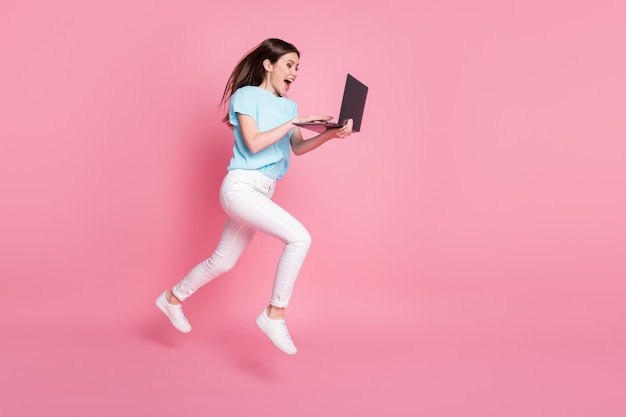 Full size photo of girl jump use laptop online discounts wear blue t-shirt pants trousers isolated pastel color background