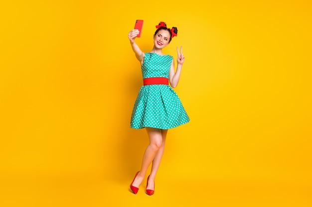 Full size photo of girl use smartphone make v-sign selfie wear skirt high-heels legs isolated shine color background