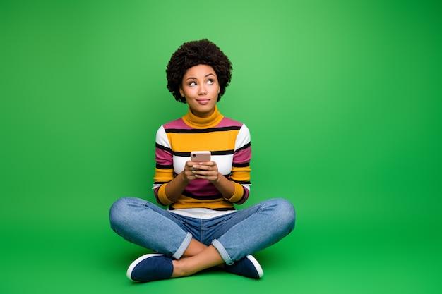 Полноразмерная фото настроенная афро-американская девушка сидит, скрестив ноги, сложа, использует сотовый телефон, ведение блога, думает, типа мысли, публикации в социальных сетях, носит джинсовую одежду