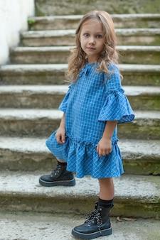 Полноразмерное фото очаровательного ребенка, стоящего на ступеньках в голубом платье.