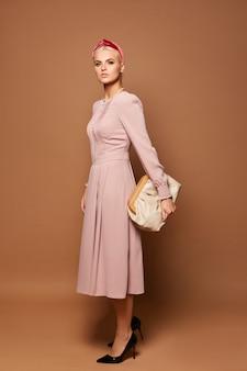무도회 밤 사진을 위해 포즈를 취하는 예쁜 모델 아가씨의 풀 사이즈 사진은 귀여운 핑크 드레스를 입습니다.