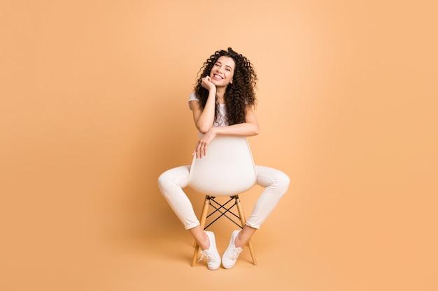 작업 일을 시작하기 위해 영감을 얻은 다리 사이에 편안한 의자에 앉아있는 놀라운 아가씨의 전체 크기 사진 캐주얼 의류 격리 베이지 색 파스텔 색상 배경