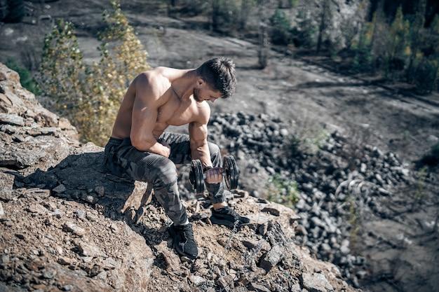 採石場で岩を持ってポーズをとっている運動選手のフルサイズの写真。屋外ショット。ボディービルダー。採石場の背景。閉じる。手にダンベル。