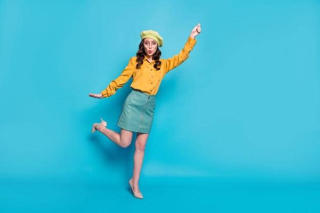 Полноразмерная фотография изумленной смешной девушки в стиле фанк, держащей руку, представьте, что она ловит воздух, летать с зонтиком, дует ветер, носить красивый головной убор, изолированный на синем цветном фоне