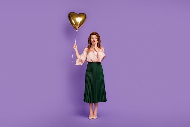 Полноразмерное фото удивленной девушки, получившей воздушный шар на праздновании юбилея