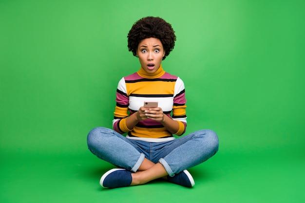 Полноразмерная фотография изумленной девушки, сидящей, скрестив ноги, скрестив ноги, использует мобильный телефон, ведение блога, впечатлен комментарий в социальных сетях, репост пост, крик, омг, носите яркую одежду