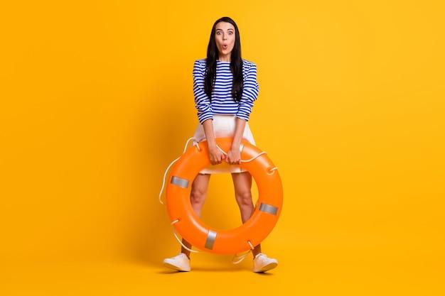 驚いた女の子の観光客のフルサイズの写真は、救命浮き輪に感銘を受けた水海の海を見つめる昏迷omgは、明るい輝きの色の背景の上に隔離された格好良い服を着ます