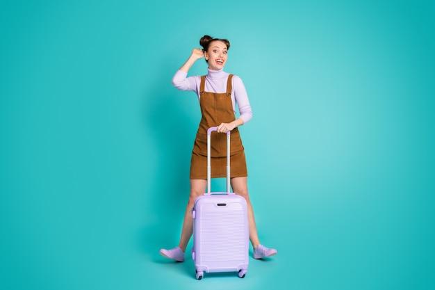 Полноразмерная фотография привлекательной веселой забавной милой симпатичной леди, ожидающей регистрации на самолет, слышит имя, держит чемодан, носит коричневое платье, фиолетовые туфли-пуловеры, изолированные на фоне бирюзового цвета