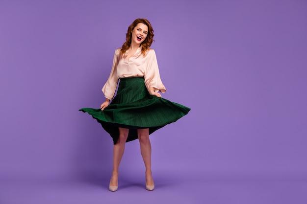 Полноразмерное фото привлекательной милой девушки, держащей свою юбку, поворачивающуюся, наслаждайтесь