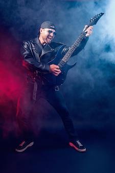 가죽 재킷과 선글라스를 쓴 잔인한 수염 난 헤비메탈 뮤지션의 풀 사이즈 사진이 블랙에 매우 감정적으로 전기 기타를 연주하고 있습니다.