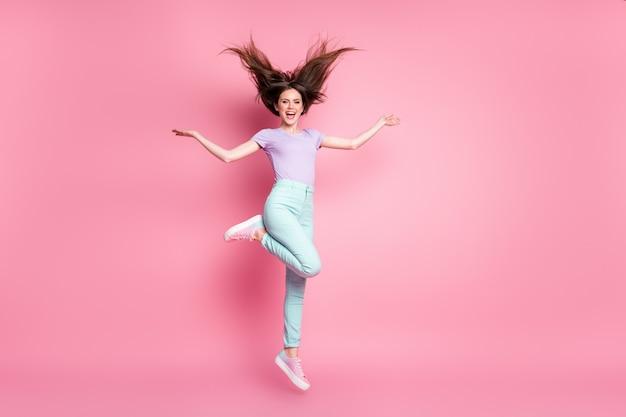 Полноразмерная фотография откровенной красивой девушки прыгает, держась за руку, радуйтесь, весенний уик-энд, отдых, расслабьтесь, наденьте фиолетовую одежду, обувь, изолированную на розовом цветном фоне