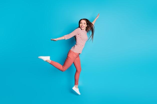 부주의한 소녀 점프의 전체 크기 사진은 주말 자유 시간 가을 여행을 즐기고 파란색 배경에 격리된 멋진 분위기의 옷을 입는다