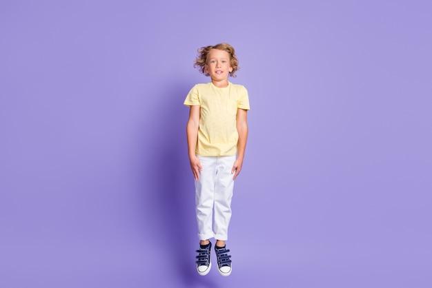 파스텔 보라색 배경 위에 격리된 캐주얼 스타일의 운동화를 신고 점프하는 매력적인 소년의 전체 크기 사진