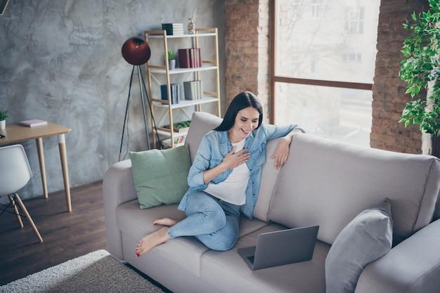 Полноразмерное фото очаровательной милой позитивной девушки в хорошем настроении у covid19 на карантине использовать ноутбук часы смешные сериалы смеяться сидеть на диване в помещении в квартире