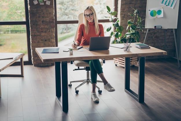 매력적인 긍정적 인 ceo 기업가 앉아 의자 테이블 작업 컴퓨터 쓰기 카피 북 계획 파트너십 회의의 전체 크기 사진 사무실 로프트 직장에서 시작 프로젝트 수행