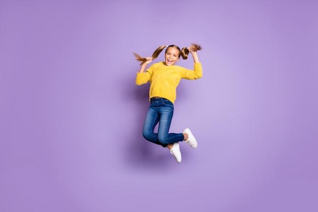 Полноразмерная фотография веселого откровенного ребенка с косичками в прыжке, наслаждающегося осенними праздниками в повседневной одежде, изолированной на стене фиолетового цвета