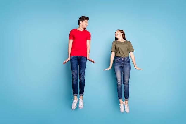 Полноразмерная фотография веселых очаровательных двух супругов расслабиться, отдохнуть, прыгнуть, насладиться весенними выходными в красивой одежде, изолированной на пастельном цветном фоне
